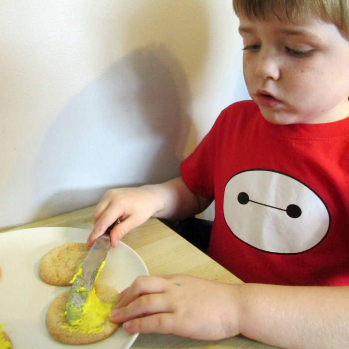 Charlie spreading icing Minions cookies