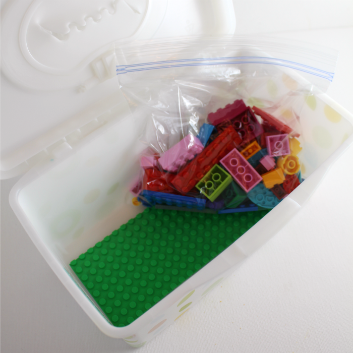 LEGO building in a wipes container